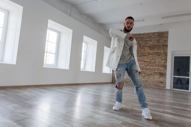 Attraktive tänzerin in einer modischen jacke und stilvollen zerrissenen jeans tanzen