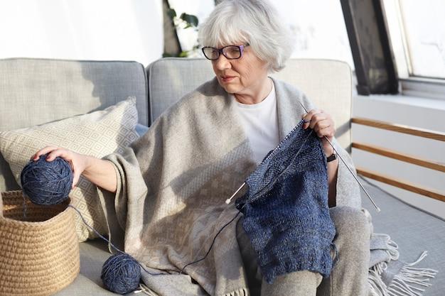Attraktive talentierte kaukasische großmutter mit brille, die ihr hobby genießt, bequem auf dem sofa zu sitzen, garnball und knie zu halten und pullover für ihren ehemann zu stricken. menschen, alter und freizeit