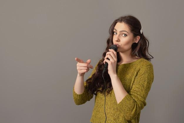 Attraktive teenagerfrau, die mit einem mikrofon gegen graue wand spricht