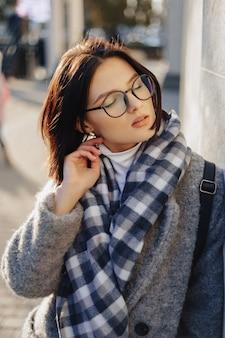 Attraktive tragende gläser der jungen frau in einem mantel gehend an einem sonnigen tag