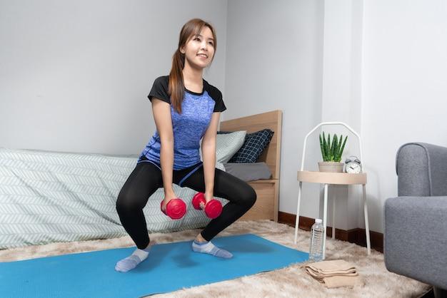 Attraktive und gesunde junge asiatische frau, die zu hause trainiert