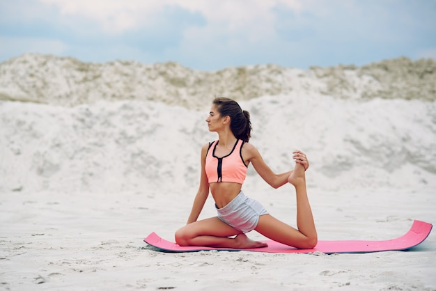 Attraktive und gesunde junge frau, die bei sonnenaufgang übungen am strand macht