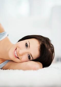 Attraktive und lächelnde frau, die auf dem teppich liegt