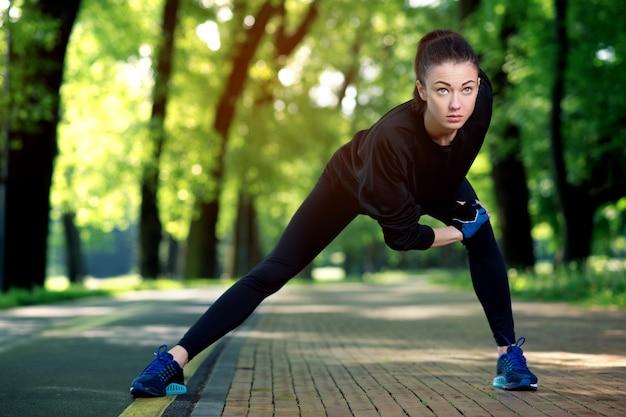 Attraktive und starke frau, die sich vor fitness im sommerpark ausdehnt. sportkonzept. gesunder lebensstil