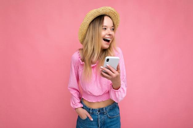 Attraktive verblüffte junge blonde frau, die lächelt und spaß hat, isoliert über rosa wand zu stehen und hand in der tasche hält rosa bluse und sommerhut unter verwendung des mobiltelefons, das zur seite schaut.