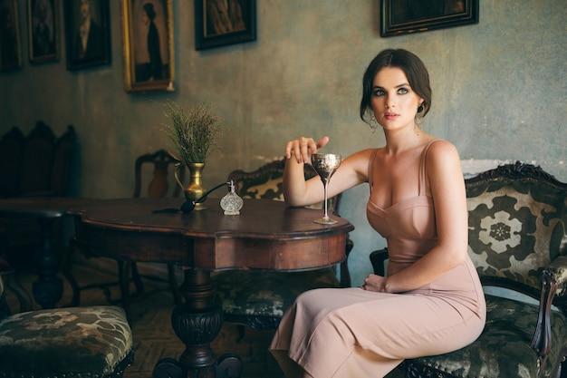 Attraktive verführerische sinnliche stilvolle frau im boho-kleid sitzend vintage retro-café, das wein aus glas trinkt