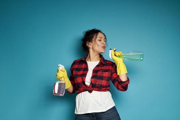 Attraktive verspielte frau, eine hausfrau, hält ein reinigungsspray wie eine pistole in den händen und bläst schießpulver wie nach einem schuss ab