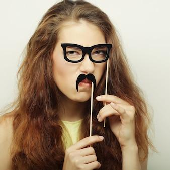 Attraktive verspielte junge frau, die schnurrbart und brille hält