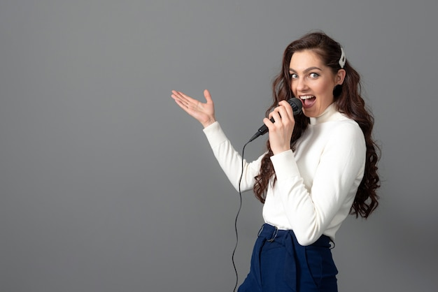 Attraktive weibliche konferenzsprecherin während der präsentation, hält mikrofon und macht einige gesten, isoliert auf grau