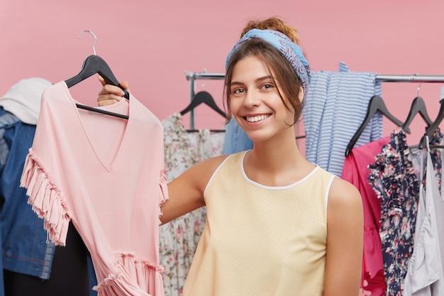 Attraktive weibliche modedesignerin, die kleiderbügel mit stilvollem rosa oberteil hält und neue sommerkollektion in ihrem ausstellungsraum präsentiert