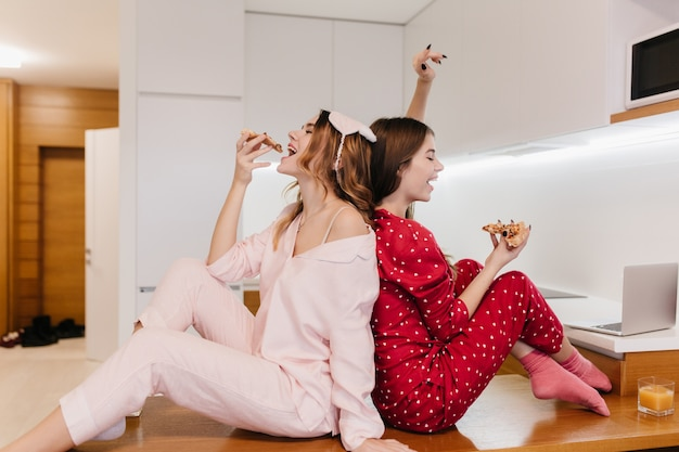 Attraktive weibliche modelle in niedlichen socken, die auf holztisch in der küche sitzen. raffinierte mädchen im pyjama, die zu hause käsepizza genießen.