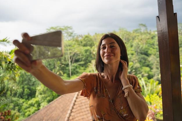Attraktive weibliche person, die ein lächeln auf ihrem gesicht hält und auf den bildschirm ihres mobiltelefons schaut