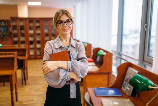 Attraktive weibliche person mit büchern in der bibliothek