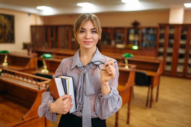 Attraktive weibliche person mit büchern in der universitätsbibliothek. frau, die im wissensdepot, bildung studiert