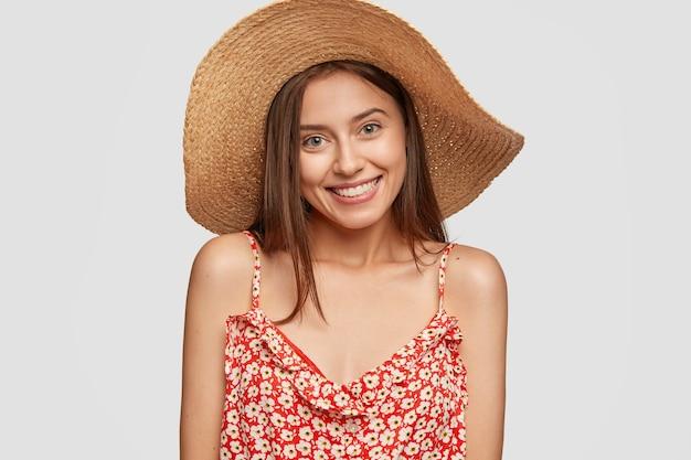 Attraktive weibliche reisende mit freundlichem, angenehmem lächeln, trägt einen stilvollen hut, gekleidet in ein modisches kleid