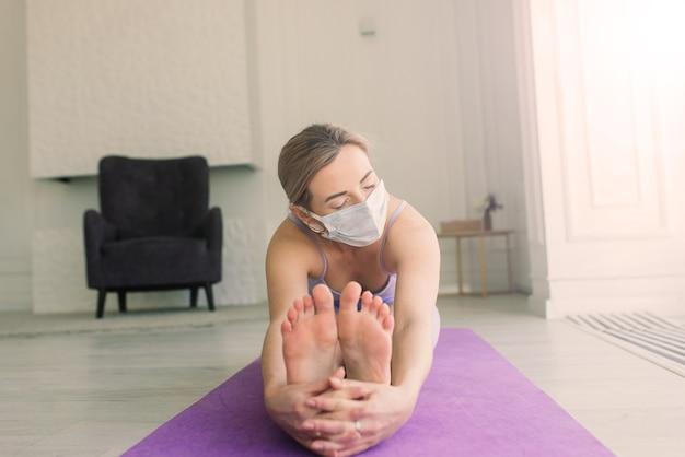 Attraktive weibliche sport-fitness-trainerin mit weißer medizinischer maske macht übungen auf der yogamatte zu hause.