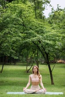 Attraktive yogalehrerin im park meditiert