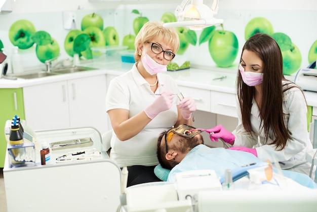 Attraktive zahnärztin lächelt in die kamera, während sie medizinische instrumente bereit hält