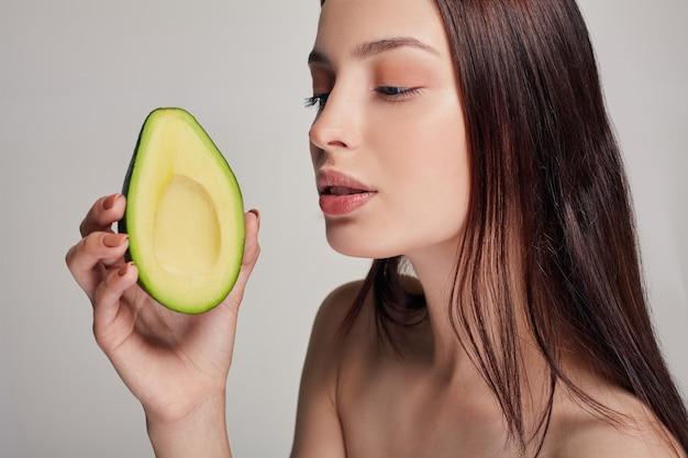 Attraktive zarte nackte dame, die avocado betrachtet