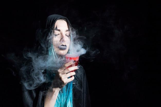 Attraktive zauberin, die becher mit rotem rauchigem alkohol hält