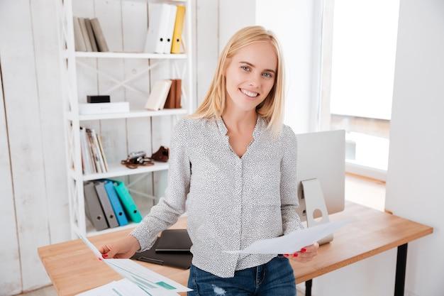Attraktive zufällige geschäftsfrau, die dokumente hält und auf dem schreibtisch sitzt