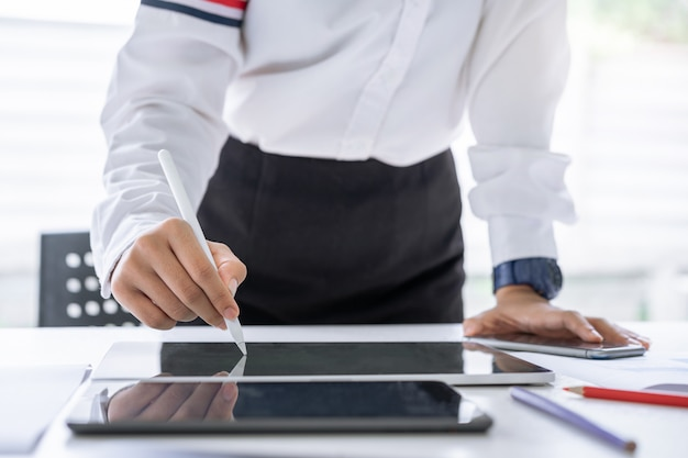Attraktive zufällige kaukasische geschäftsfrau, die ein digitales stiftschreiben auf tablette bei der stellung in einem büro verwendet.