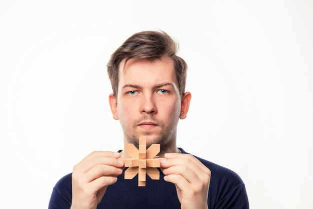 Attraktiver 25-jähriger geschäftsmann, der mit holzpuzzle verwirrt schaut.