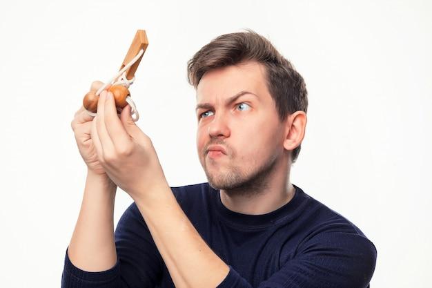 Attraktiver 25-jähriger geschäftsmann, der verwirrt auf holzpuzzle schaut.