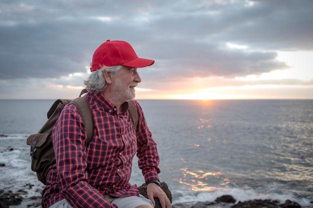 Attraktiver älterer lächelnder mann, der auf der klippe am strand mit horizont über wasser und sonnenunterganglicht sitzt. aktive glückliche rentner, die das wintermeer genießen enjoying