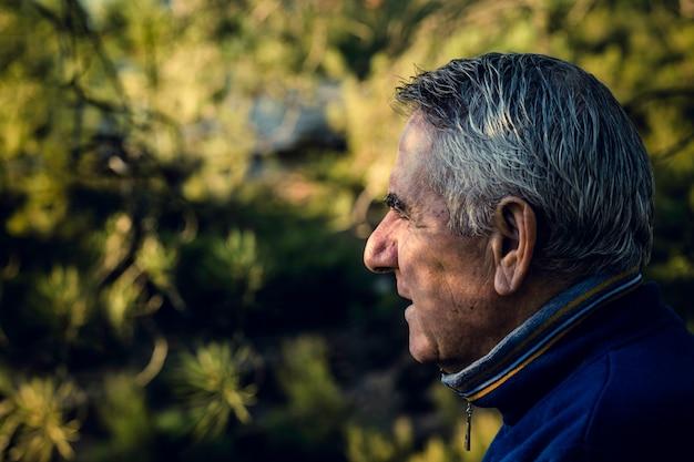 Attraktiver älterer mann mit dem grauen haar, das im vordergrund schaut