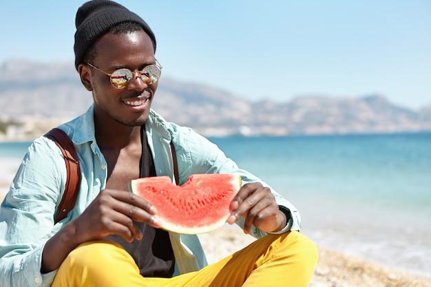 Attraktiver afrikanischer student in guter stimmung, der stilvolle kleidung und accessoires trägt, die am sonnigen tag nach dem college am strand ruhen, sich über schönes wetter am meer freuen und reife wassermelone essen