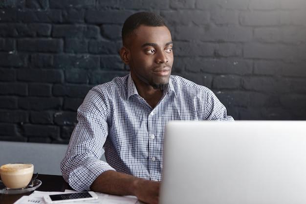 Attraktiver afroamerikanischer geschäftsmann, der fern arbeitet