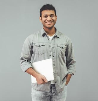Attraktiver afroamerikanischer mann hält einen laptop