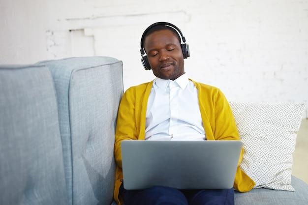 Attraktiver afroamerikanischer mann in stilvoller kleidung, der klassische musik über drahtloses schwarzes headset genießt, auf bequemer couch mit tragbarem computer auf seinem schoß sitzt und augen mit vergnügen schließt