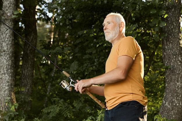 Attraktiver aktiver erfahrener älterer unrasierter fischer in seinen sechzigern, der ernsthaften gesichtsausdruck konzentriert hat, die angelrute festhält und bereit ist, fische aus dem fluss zu ziehen. erholung und freizeit