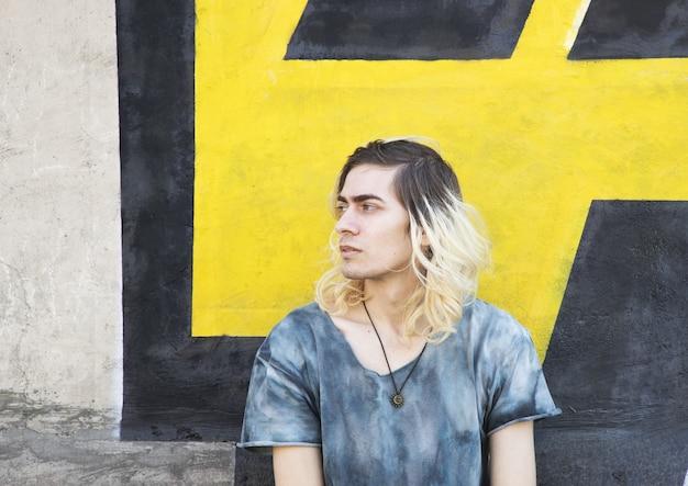 Attraktiver armenischer kerl, der auf einer gelben und schwarzen wand wegschaut