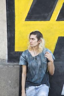 Attraktiver armenischer kerl, der auf einer gelben und schwarzen wandoberfläche wegschaut