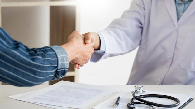 Attraktiver arzt und patient händeschütteln für ermutigung und empathie, gesundheitsversorgung und unterstützung, medizinisches konzept.