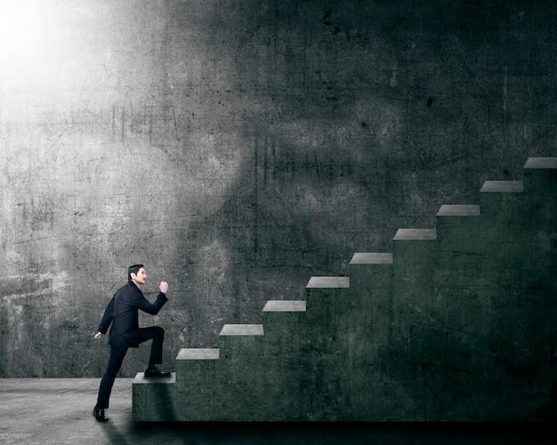 Attraktiver asiatischer geschäftsmann, der ein treppenhaus steigert