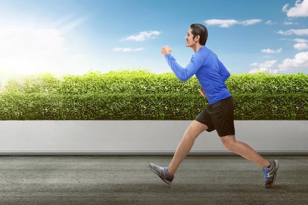 Attraktiver asiatischer mann, der am morgen läuft