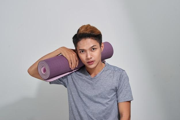 Attraktiver asiatischer mann mit yogamatte posiert in einem studio