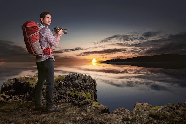 Attraktiver asiatischer reisendmann mit kamera möchten fotos machen
