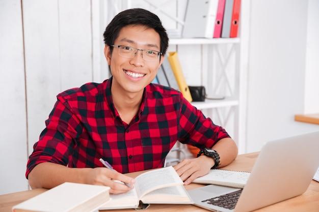 Attraktiver asiatischer student, der auf die vorderseite schaut und notizen schreibt, während er bücher liest und im klassenzimmer am laptop arbeitet