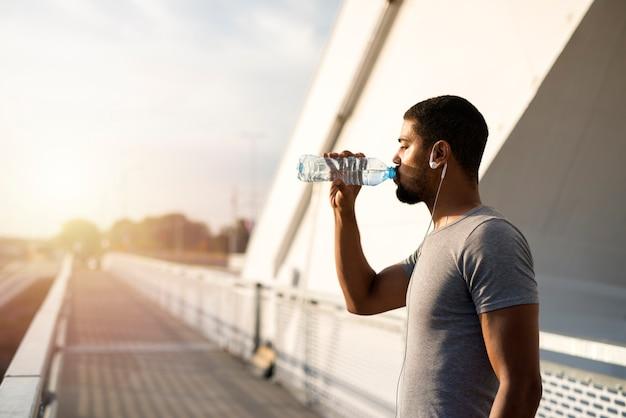 Attraktiver athlet, der eine flasche wasser hält und vor dem training trinkt