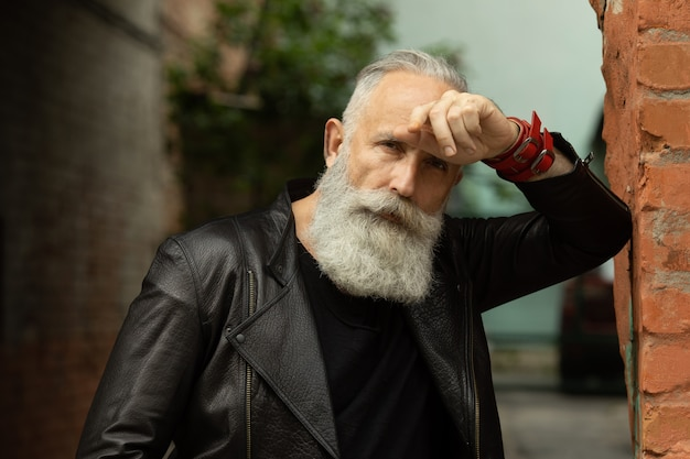 Attraktiver bärtiger älterer modellmann im städtischen kontext.