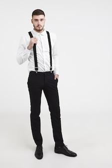 Attraktiver bärtiger bräutigam in eleganter kleidung, der sich auf seinen hochzeitstag vorbereitet, verschiedene outfits anprobiert, mit ernstem gesichtsausdruck in die kamera schaut und schwarze hosenträger zieht. vertikale studioaufnahme