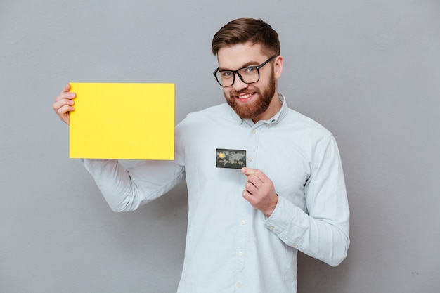Attraktiver bärtiger geschäftsmann, der leeres papier und debitkarte hält