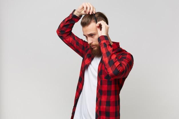 Attraktiver bärtiger junger mann im hemd, der im profil steht, das moderne frisur tut und sein haar mit kamm pflegt, der über weißem hintergrund lokalisiert wird