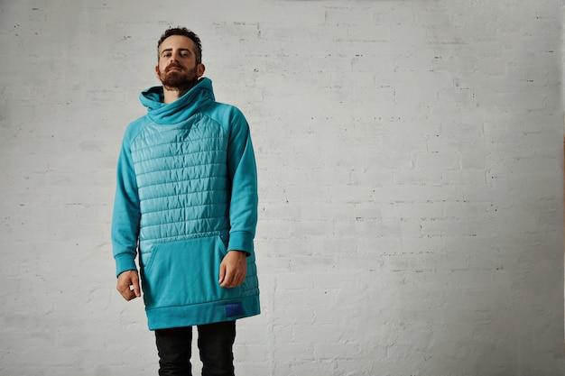 Attraktiver bärtiger junger mann in einem übergroßen warmen hellblauen gesteppten sweatshirt lokalisiert auf weiß