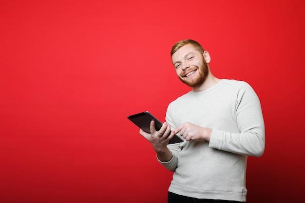 Attraktiver bärtiger kerl, der lächelt und kamera betrachtet, während er auf hellrotem hintergrund steht und moderne tablette verwendet